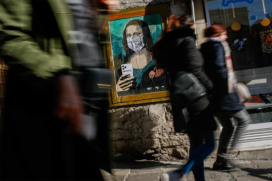 """2020年2月18日巴塞羅那的一條街道,人們在意大利城市藝術家Salvatore Benintende的海報旁走過,達芬奇的蒙娜麗莎戴上口罩,並手持"""" Mobile World Virus""""手機。 攝:Pau Barrena/AFP via Getty Images"""