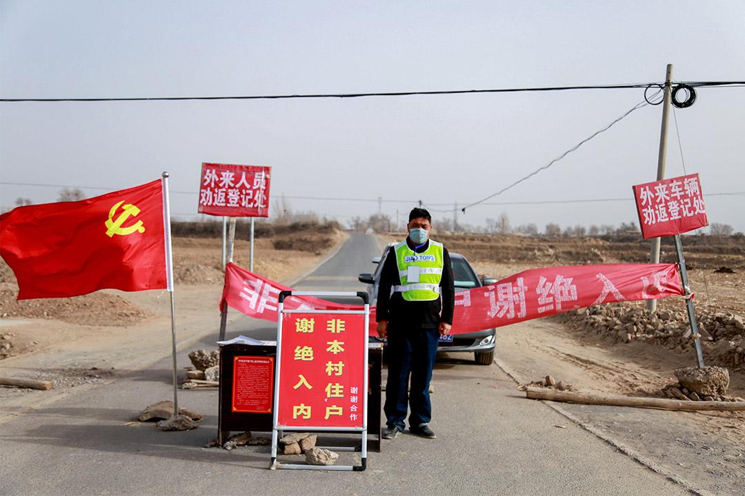 2020年2月18日,一名守衞在中國甘肅省農村的入口處,以阻止新型冠狀病毒擴散。