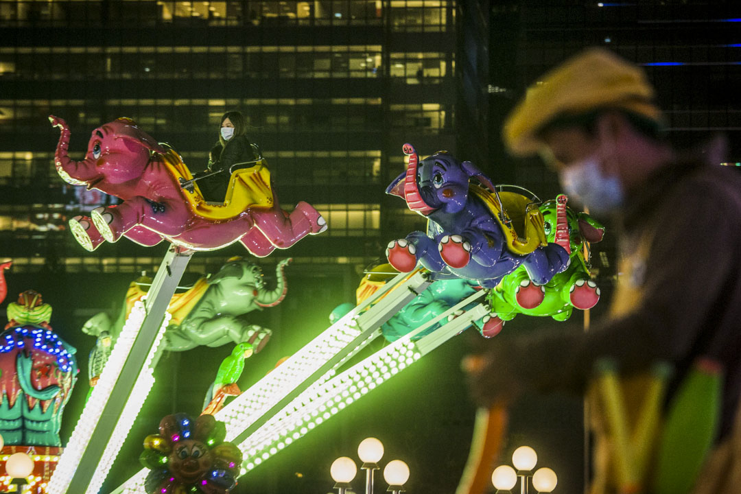 2020年2月3日,中環AIA歐陸嘉年華,市民戴著口罩玩機動遊戲。