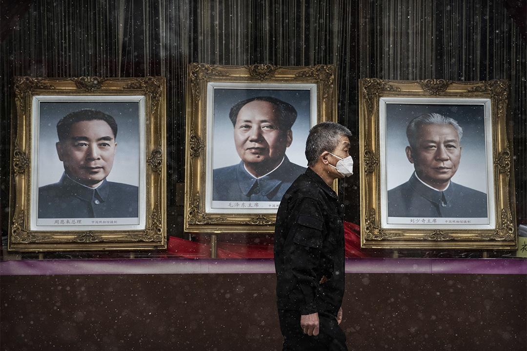 2020年2月14日中國北京,一個中國男子戴著口罩走過已故中國領導人毛澤東的照片。 攝:Kevin Frayer/Getty Images