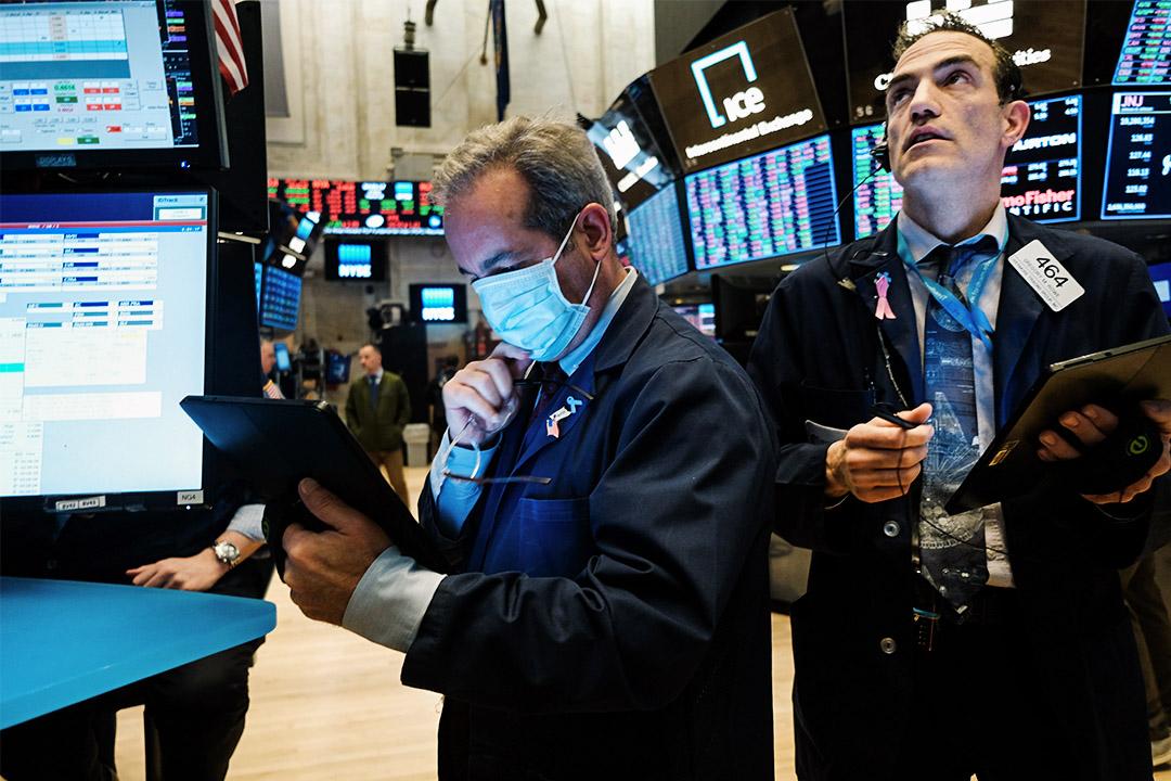 2020年3月20日美國紐約,一名交易員戴上醫療口罩在證券交易所內工作。
