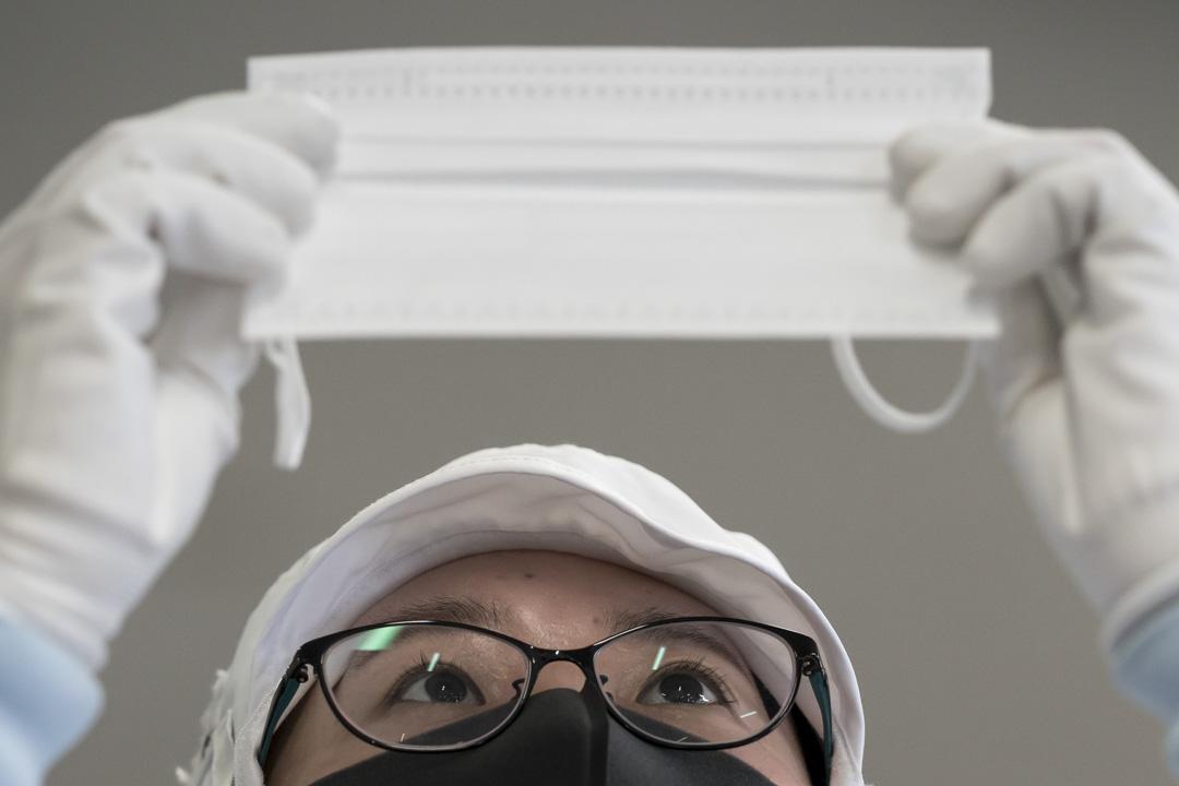 2020年2月6日,日本名古屋一間工廠的生產線上,工人檢查生產口罩的品質。