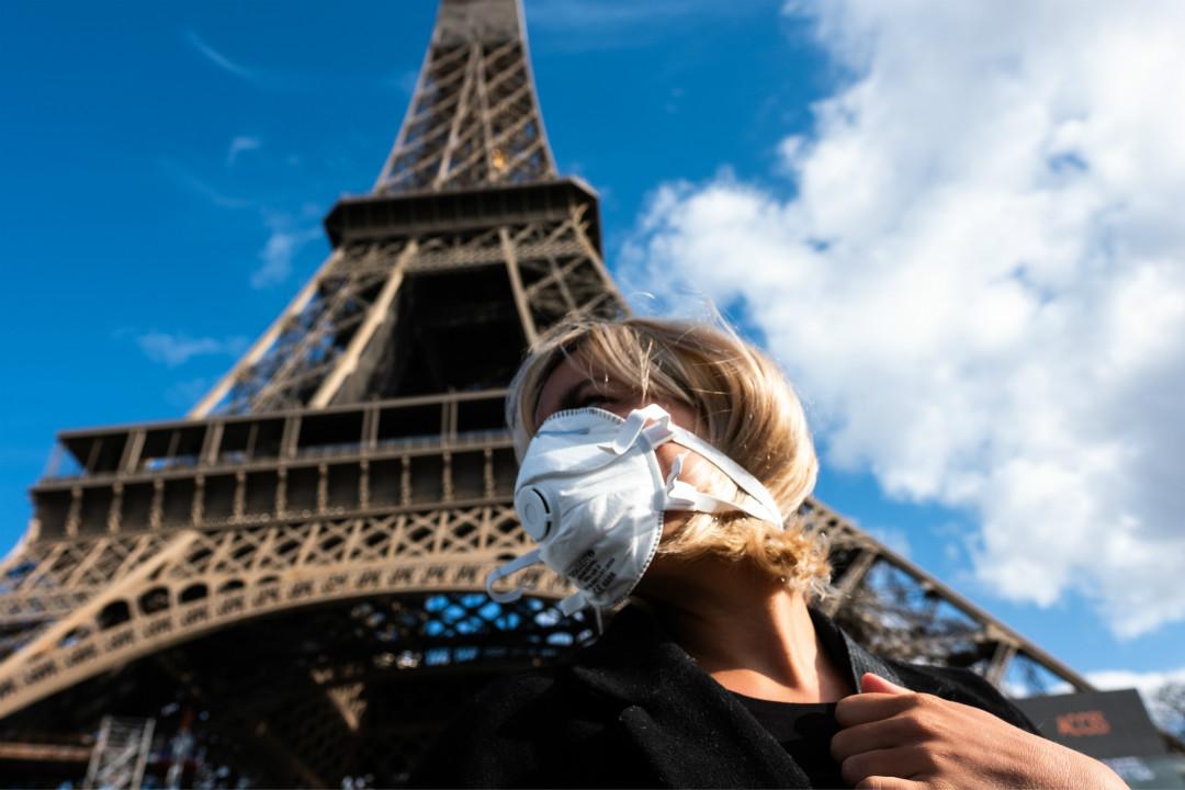 2020年3月13日,法國巴黎,一人頭戴口罩在埃菲爾鐵塔前。 攝:Jerome Gilles/Getty Images
