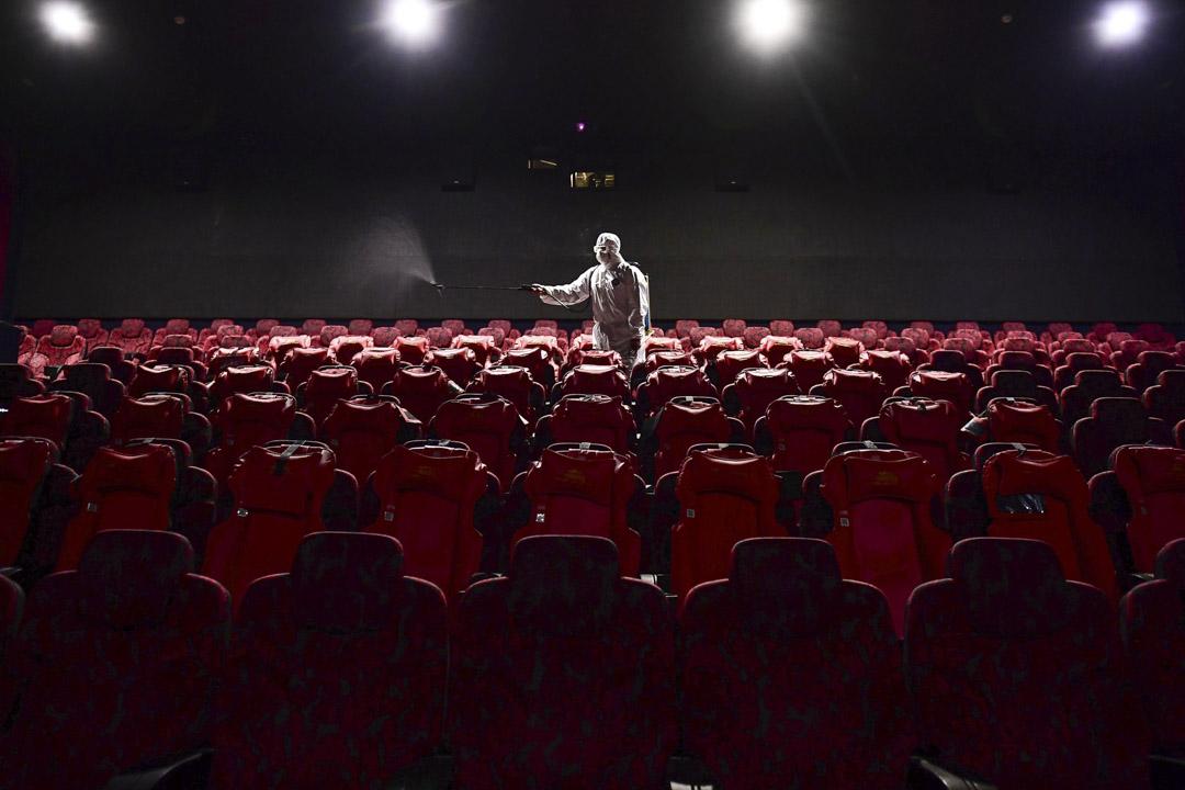 2020年3月25日,遼寧省瀋陽市,工作人員為將向公眾開放的電影院噴灑消毒劑。 攝:STR/AFP via Getty Images