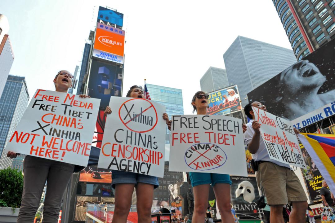 2011年8月1日,新華社在紐約時報廣場租用新電子廣告牌,當地學生在廣告牌下抗議。 攝:Stan Honda/Getty Images