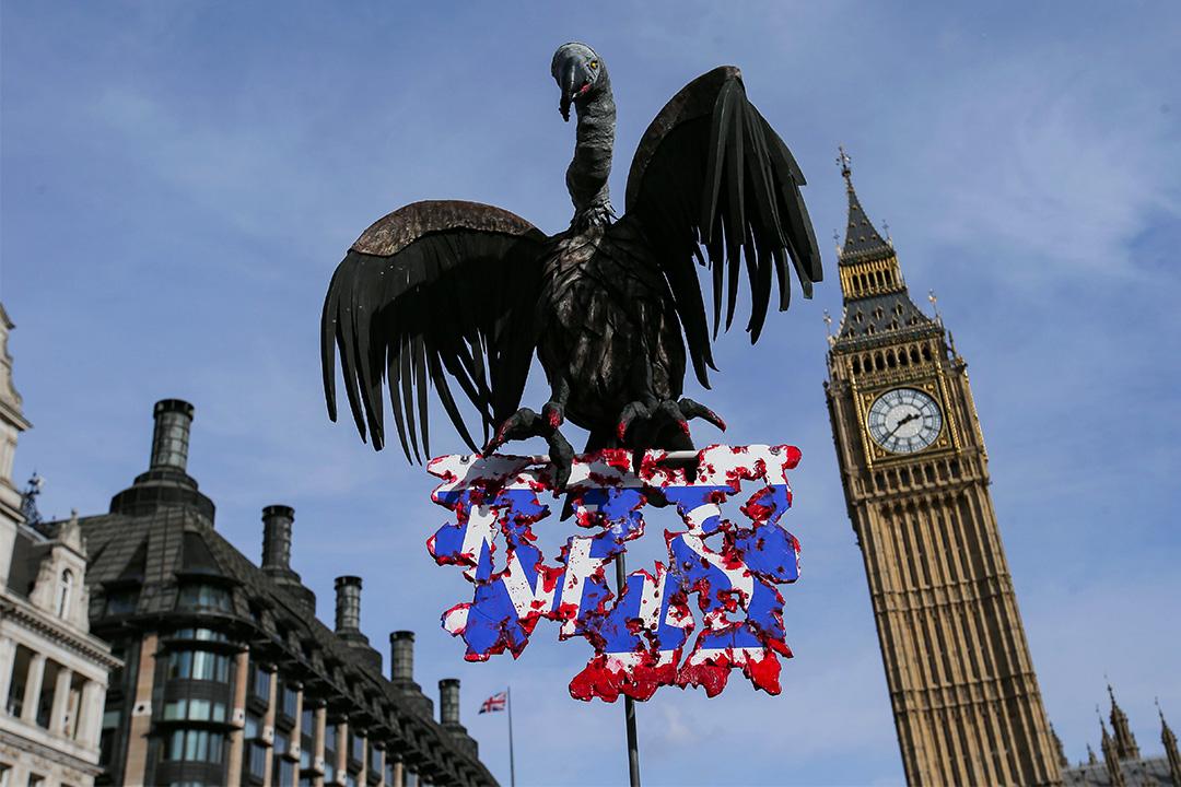2017年3月4日,在反對政府削減NHS預算的遊行中,一張貼有禿鷹模型的標語牌展示於國會大廈的大笨鐘前。 攝:Daniel Leal Olivas/AFP via Getty Images
