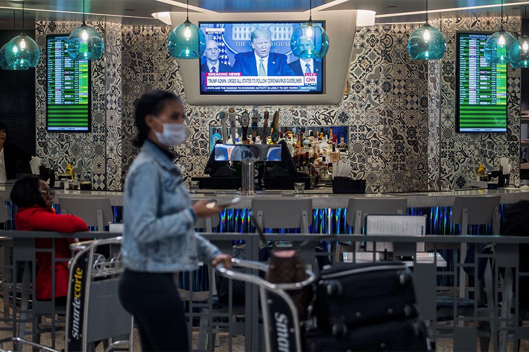 2020年3月17日,一名婦女抵達華盛頓杜勒斯國際機場並經過一家酒吧,電視上可看到美國總統特朗普在新聞發布會上講話。