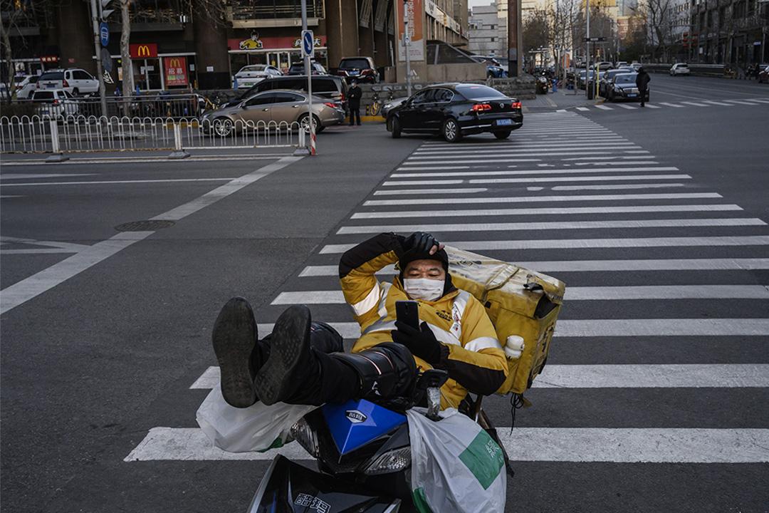 2020年2月21日中國北京,一名中國快遞員戴著口罩看著他的電話。