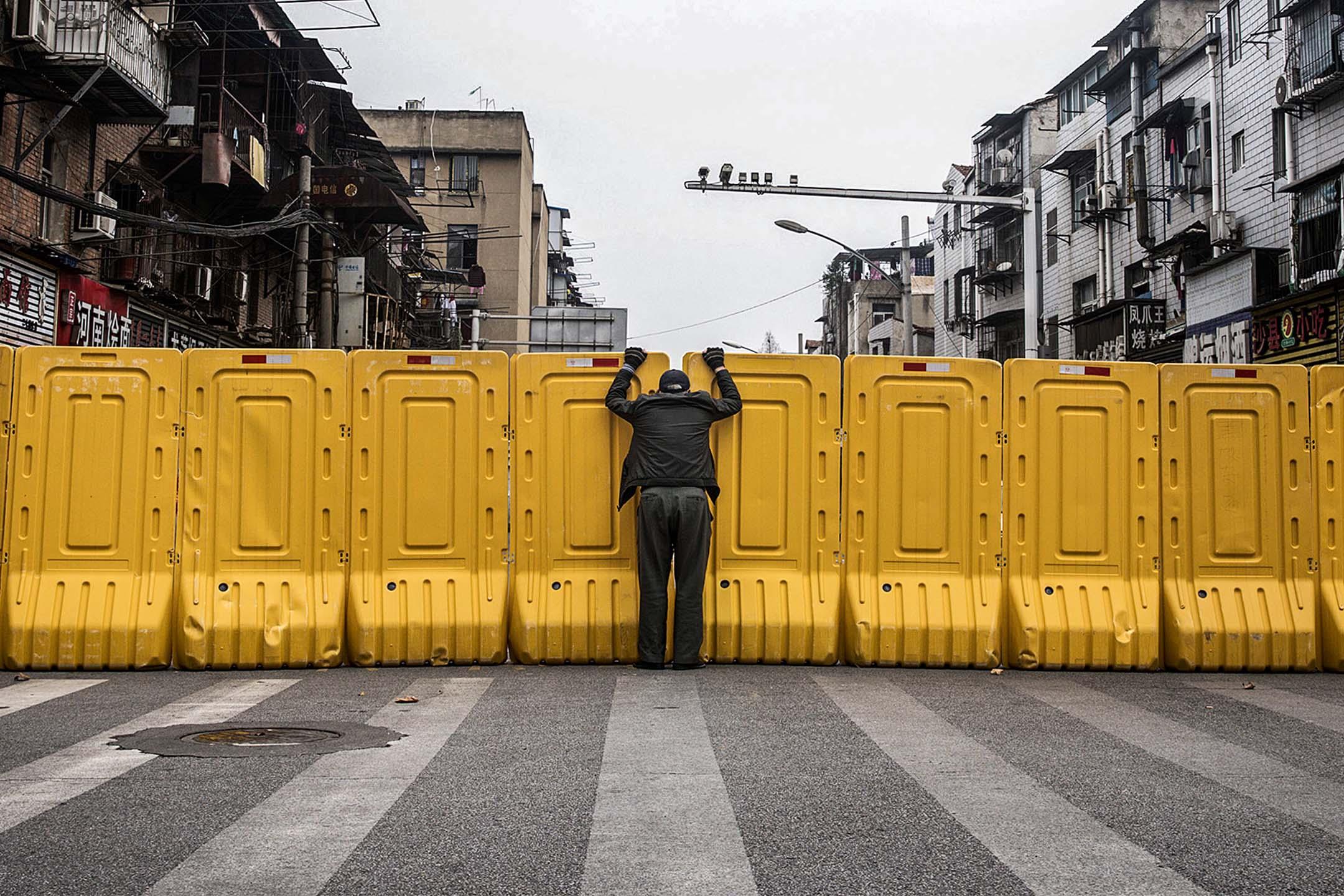 2020年3月08日中國武漢,一個戴著口罩的男人在一個臨時的隔離牆前與另一人交談,該牆是為限制住宅區居民的出入。 圖:Getty Images