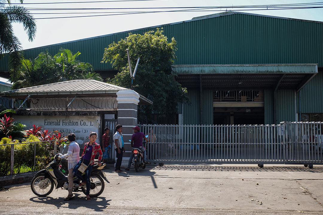 仰光工業區的工廠門口,一位父親載着女兒去找工作。