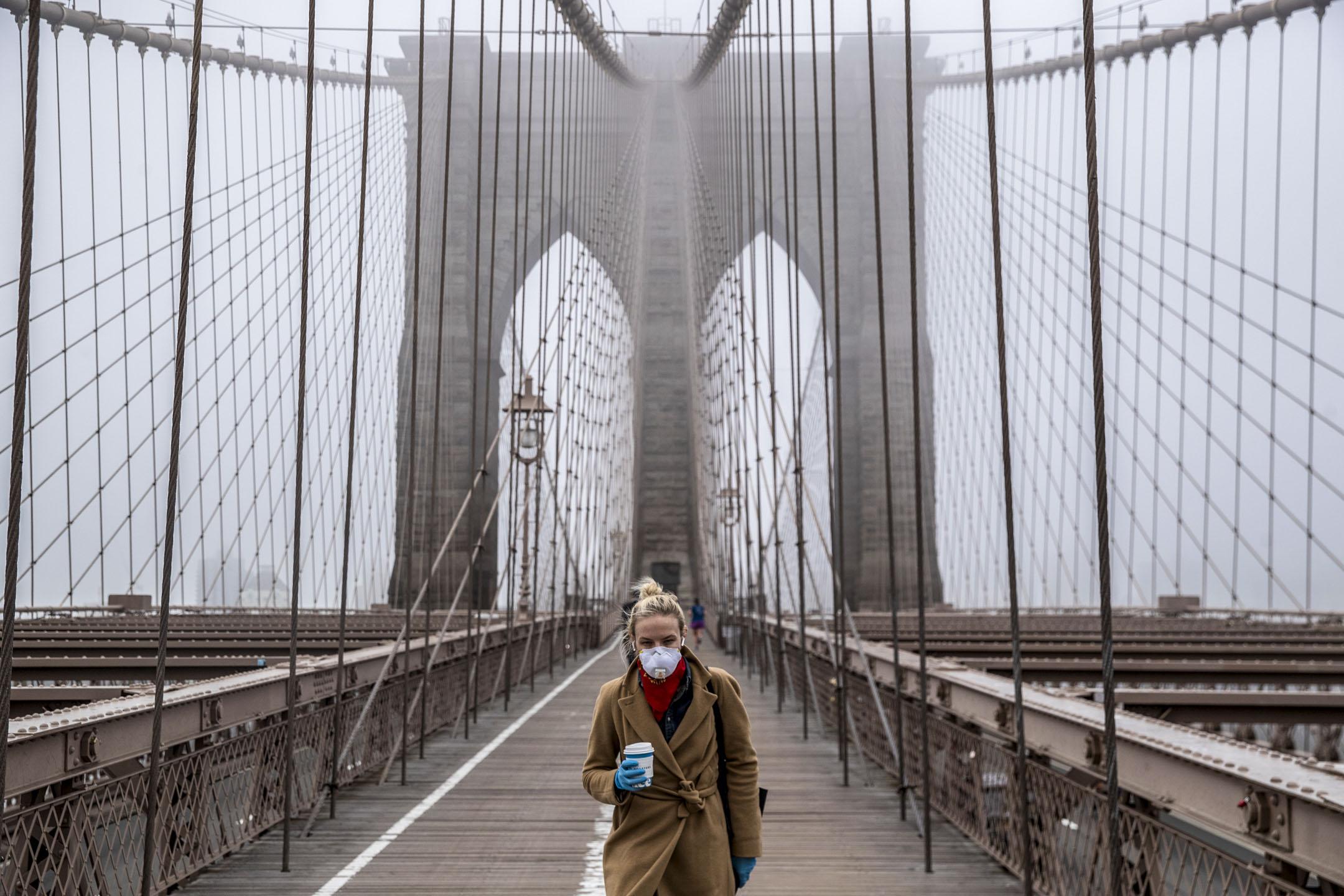 2020年3月20日,紐約布魯克林大橋上,一個戴著口罩的女子經過。 攝:Victor J. Blue/Getty Images