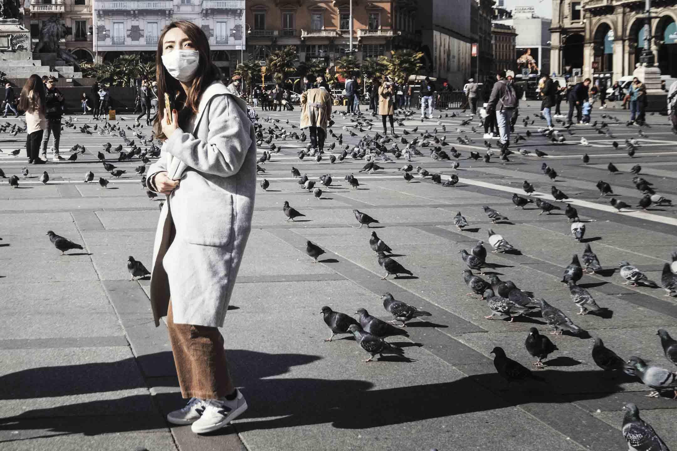 2020年2月27日,一名戴著防護口罩的遊客在意大利米蘭的大教堂廣場上。 攝:Ginamarco Maraviglia/Bloomberg via Getty Images