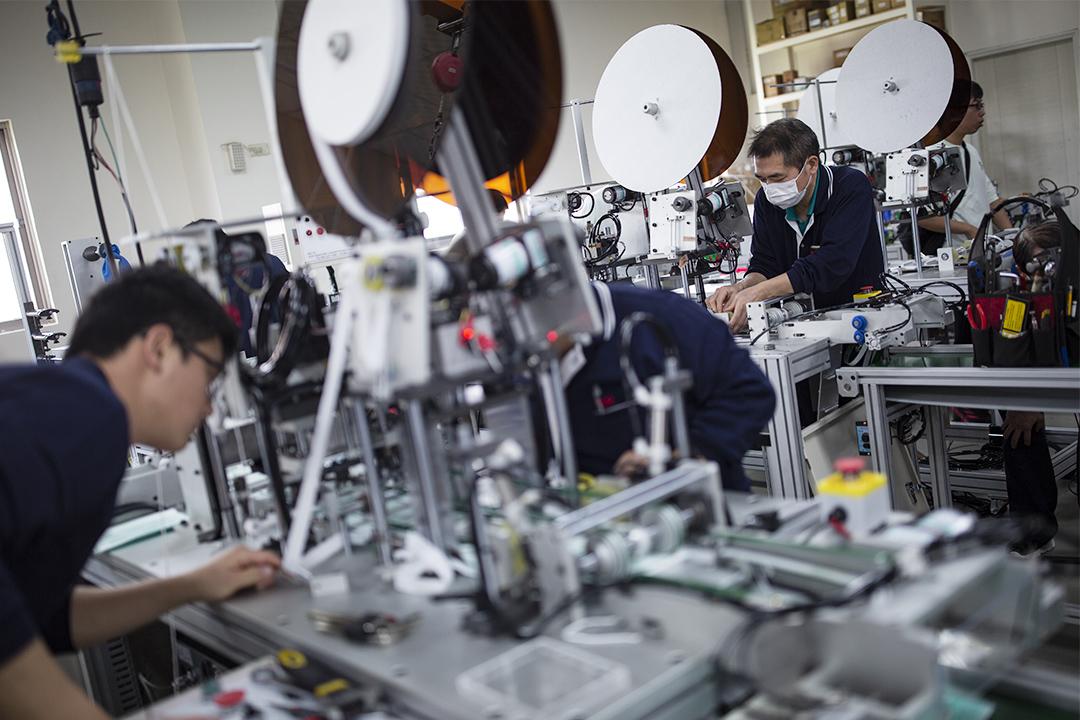 2020年2月14日,鶯歌一間口罩機台製造廠內,員工正檢查新的機器。