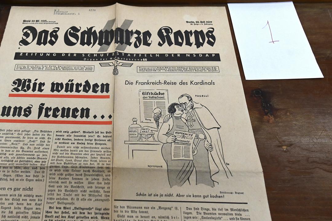 2020年3月2日,梵蒂岡解密一批檔案,其中包括納粹德國黨衛隊官媒《黑色軍團》(Das Schwarze Korps)於1937年7月22日發行的報章;報章頭版漫畫諷刺派契利樞機(即後來的教宗庇護十二世)抱擁一名象徵共產主義者的女士。 攝:Alberto Pizzoli / AFP via Getty Images