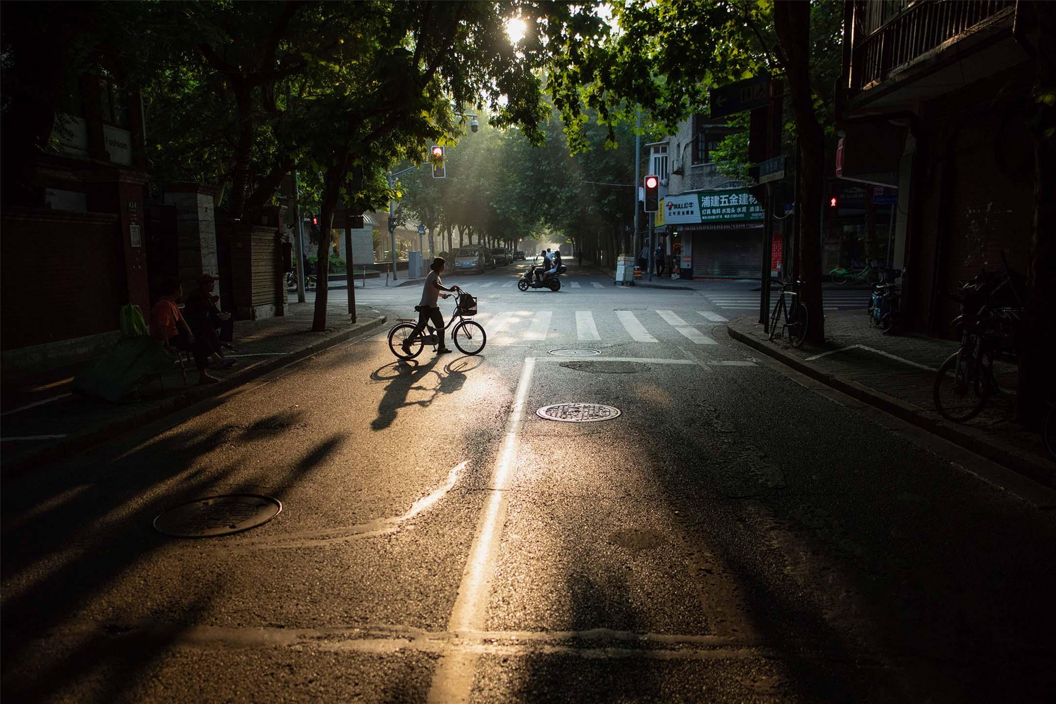 一個女人於凌晨在中國上海街頭推著她的自行車。
