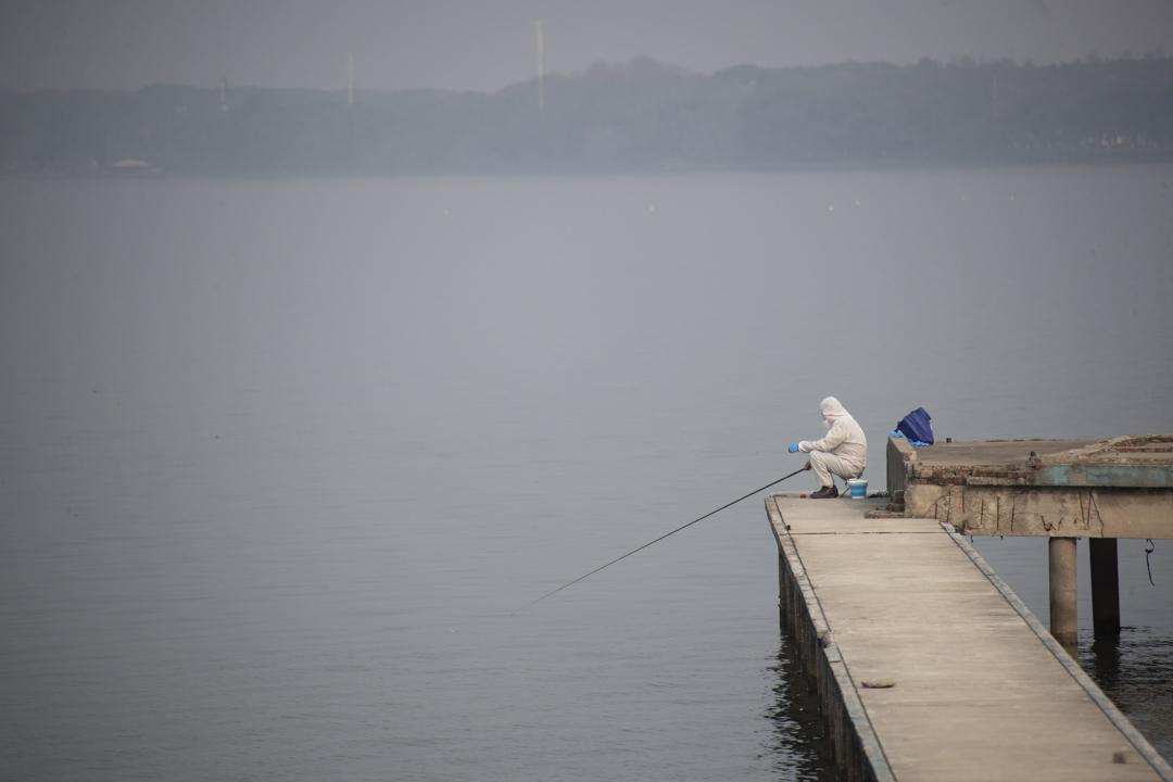 2020年2月25日,武漢有一位穿防護服在釣魚的人。
