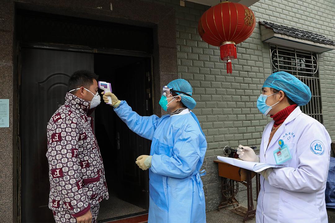2020年1月27日浙江省杭州,社區的防疫人員在檢查湖北省歸來的村民的體温。