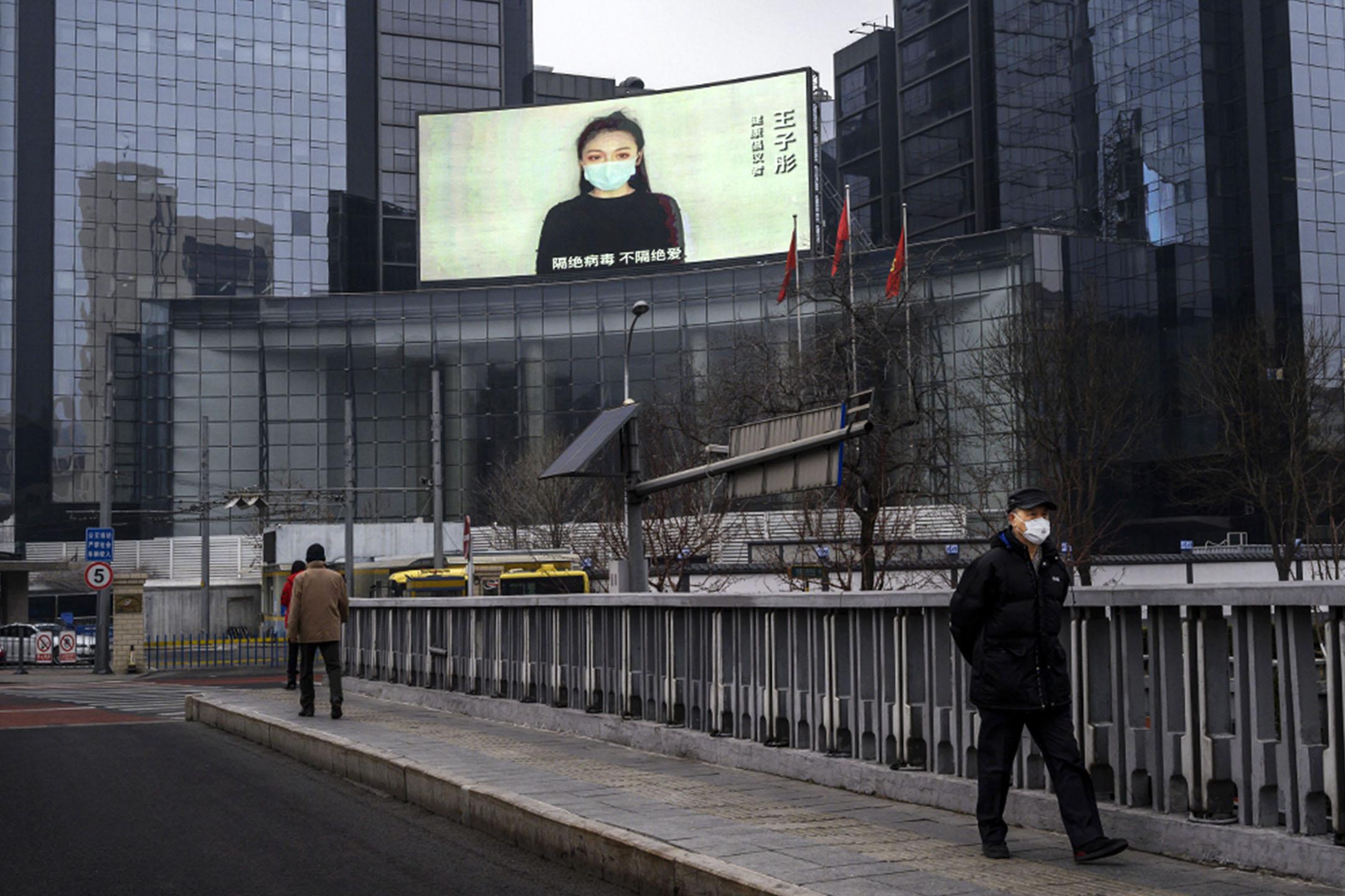 2020年2月20日在中國北京,一個大屏幕顯示一個女人的廣播,街道上一名男子戴著口罩。 攝:Kevin Frayer/Getty Images