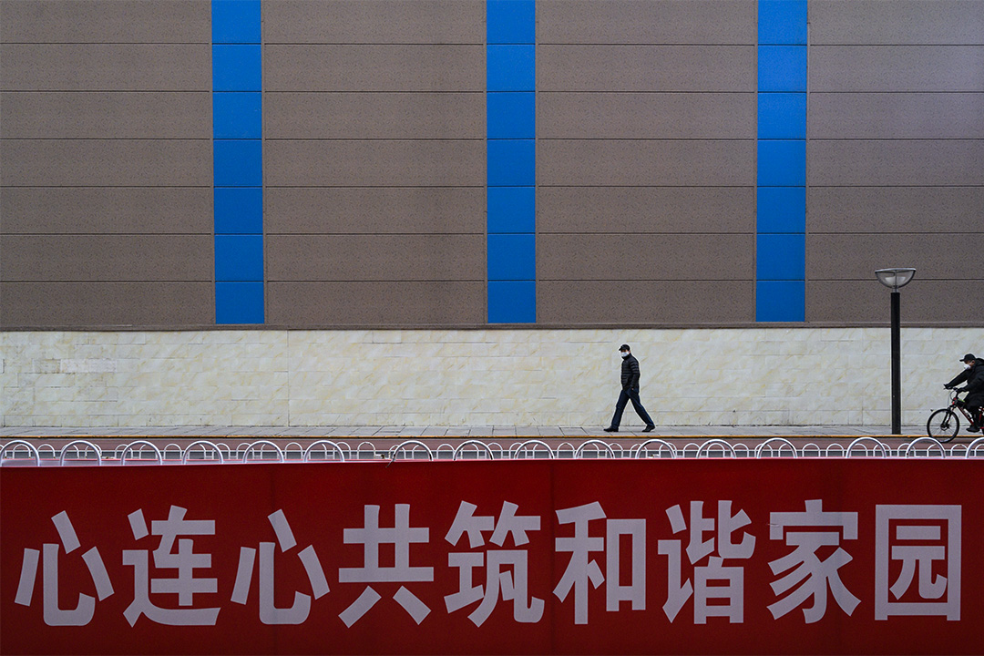 """2020年2月18日中國北京,戴著口罩的男子在商業街上走過,一宣傳橫幅上寫著""""心連心共築和諧家園""""。"""