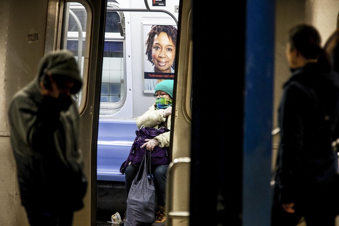 2020年3月17日,紐約地下鐵的乘客以圍巾遮臉。