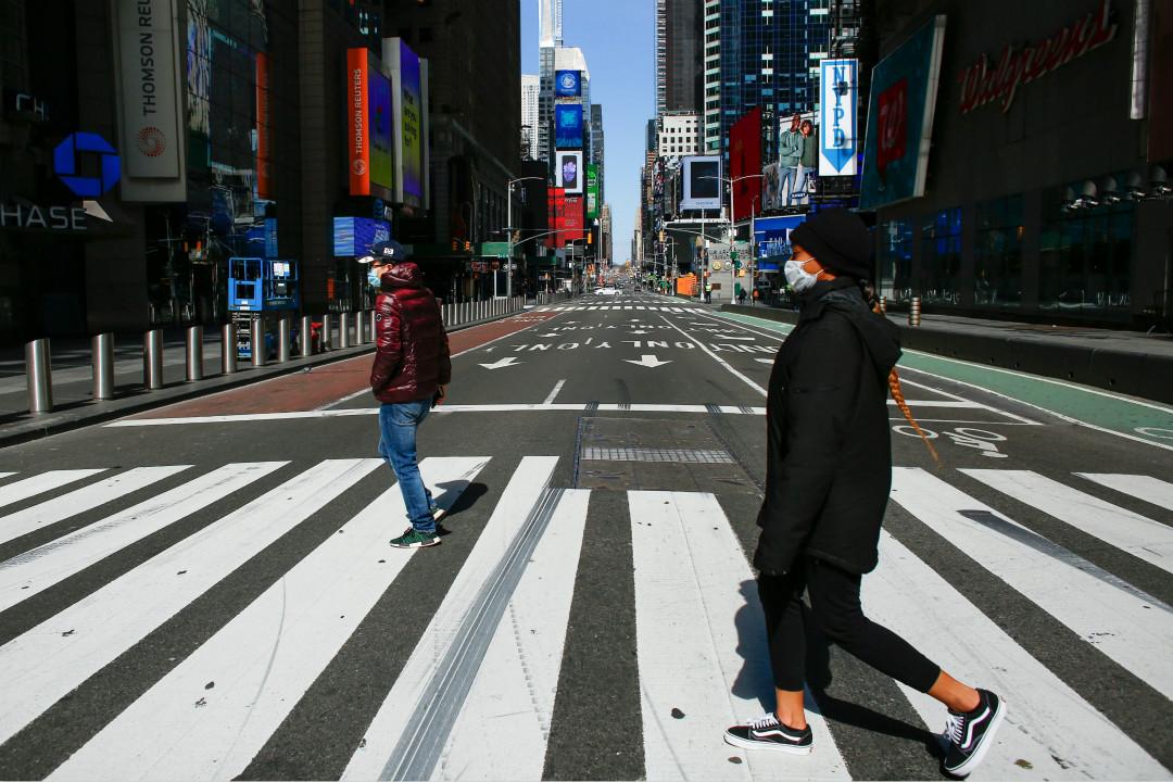 2020年3月22日,紐約時報廣場,行人戴口罩過街。 攝:Kena Betancur/Getty Images