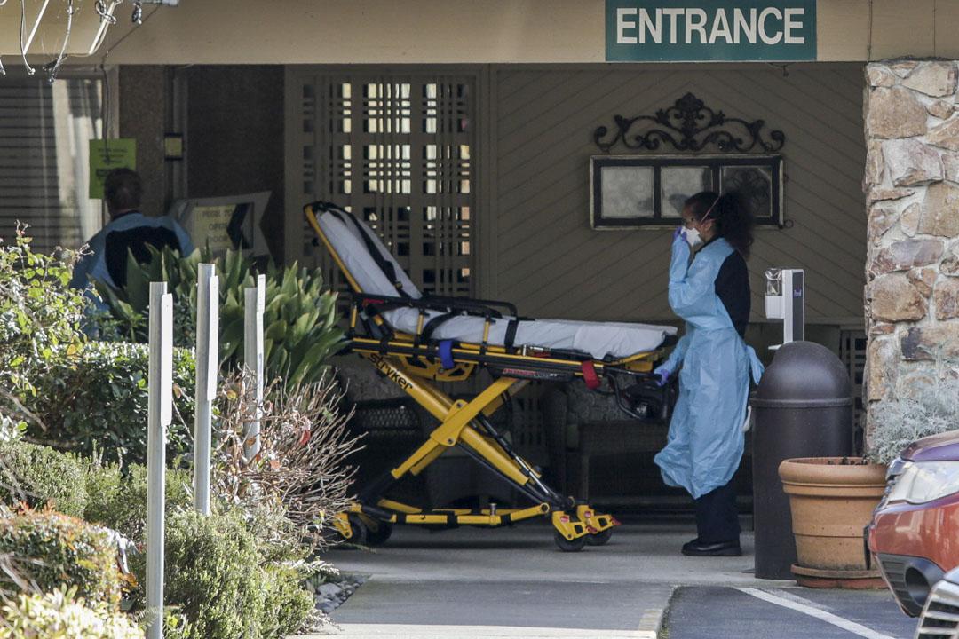 2020年2月29日,華盛頓一間護理中心的一名員工和一名居民被診斷出患有新冠病毒,醫護人員到場準備將他們運離現場。 攝:Jason Redmond/AFP via Getty Images