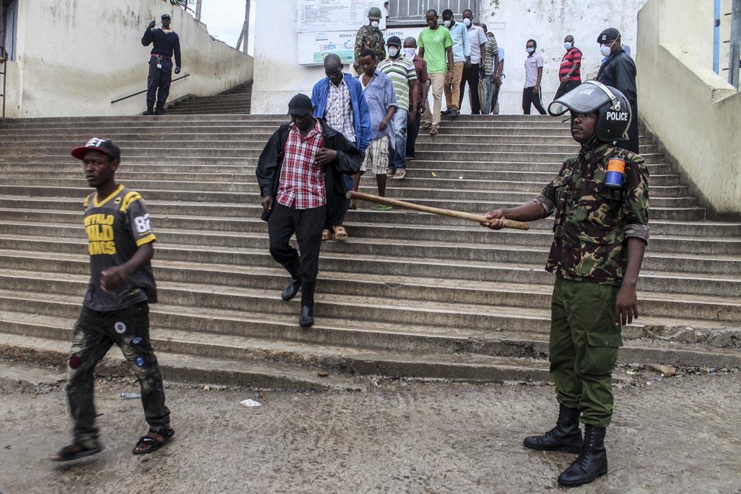 2020年3月27日肯尼亞蒙巴薩,上班的市民在警察旁走過前往渡船。
