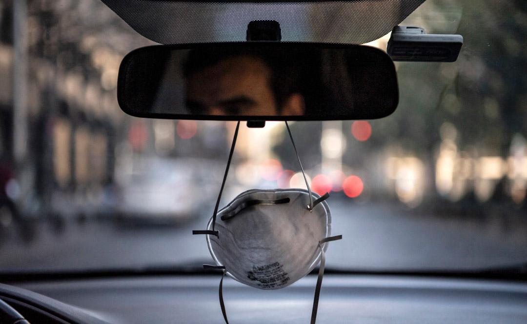 2020年4月6日,智利聖地亞哥在新冠狀病毒大流行中,一輛汽車的倒後鏡懸掛了一個口罩。 攝:Martin Bernetti/AFP via Getty Images