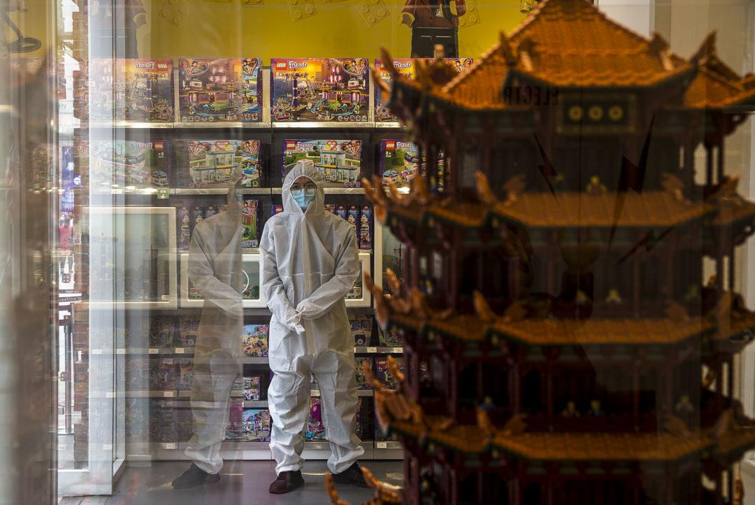 武漢漢街,店員穿防護服守在門口,等著為進門的顧客測量體溫。