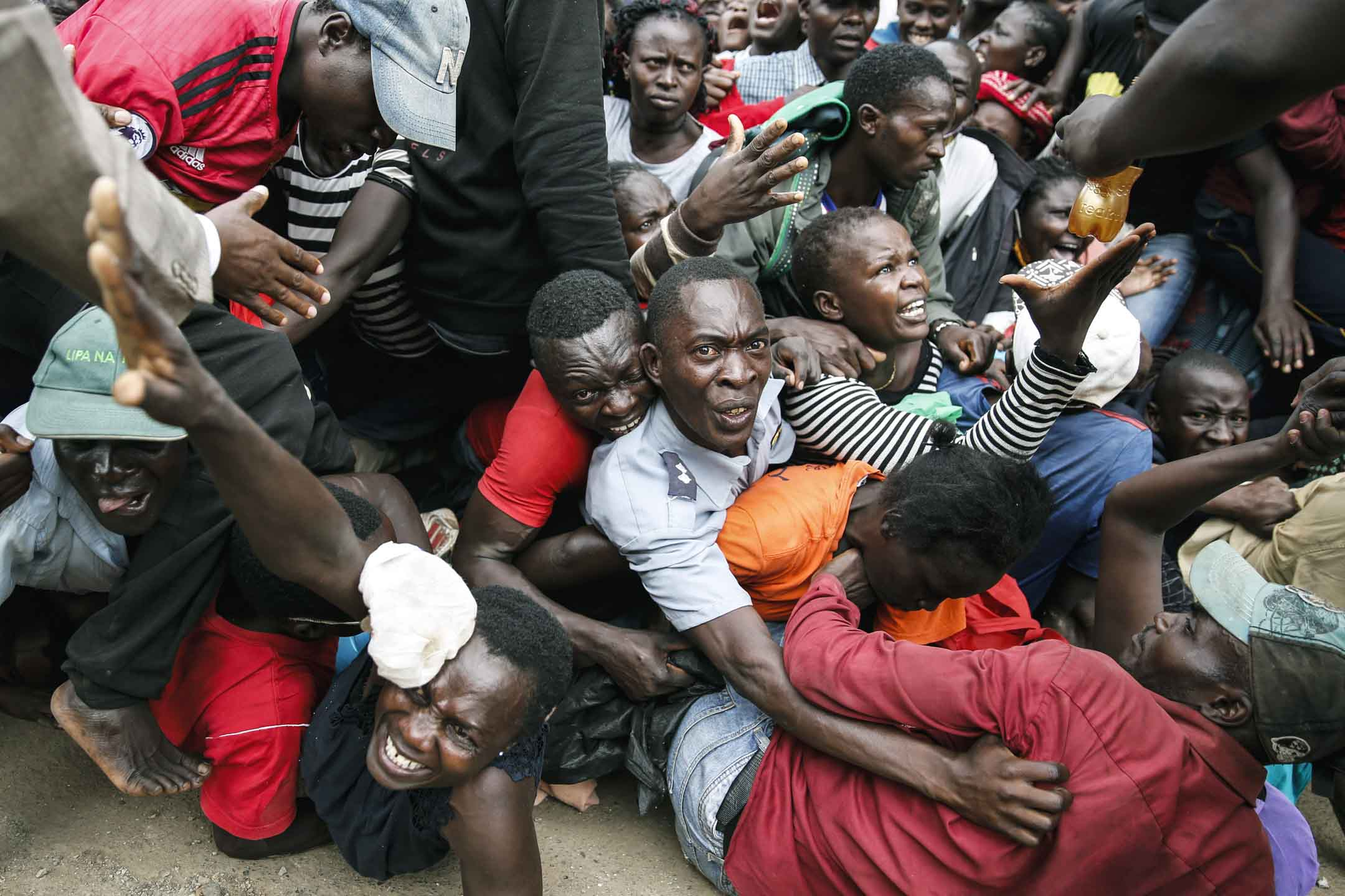 2020年4月10日肯尼亞內羅畢,因2019冠狀病毒被隔離的居民於分派食物時發生混亂,導致警察施放催淚瓦斯,事件造成一些居民受傷 。 攝:Brian Inganga/AP/達志影像
