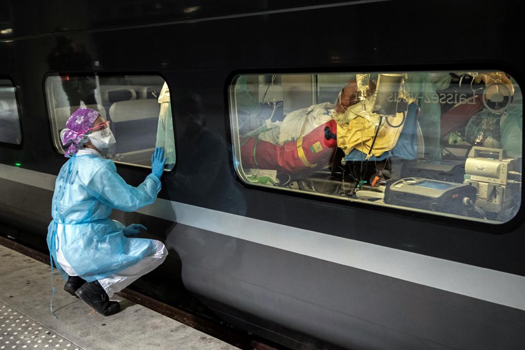 2020年4月1日巴黎的火車站月台上,醫務人員透過高速列車的窗戶觀看,以從巴黎地區運送感染2019冠狀病毒的患者至其他地區。