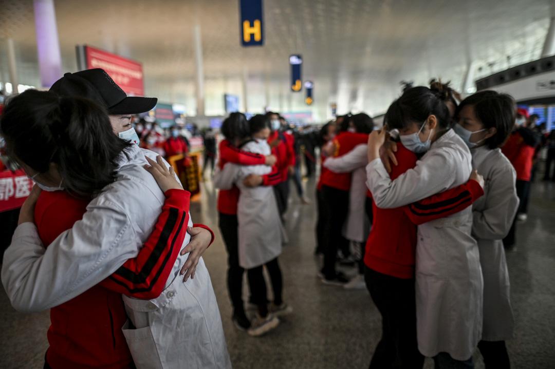 2020年4月8日,來自吉林省的醫護人員完成抗疫工作,在天河國際機場和武漢的醫護人員相擁道別。 攝:Hector Retamal/AFP via Getty Images