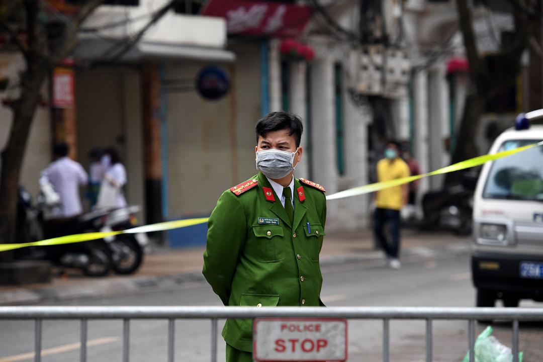 2020年3月8日在越南首都河內,一名佩戴口罩的警員正巡視隔離區域。 攝:Nhac Nguyen / AFP via Getty Images