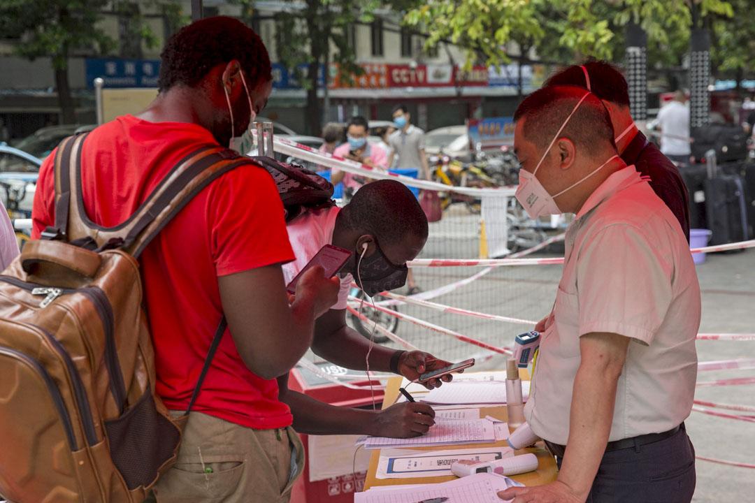 2020年4月18日,廣州大沙頭綠蔭路,在盛賢二手市場入口,兩名非洲男子在進入前登記個人信息。