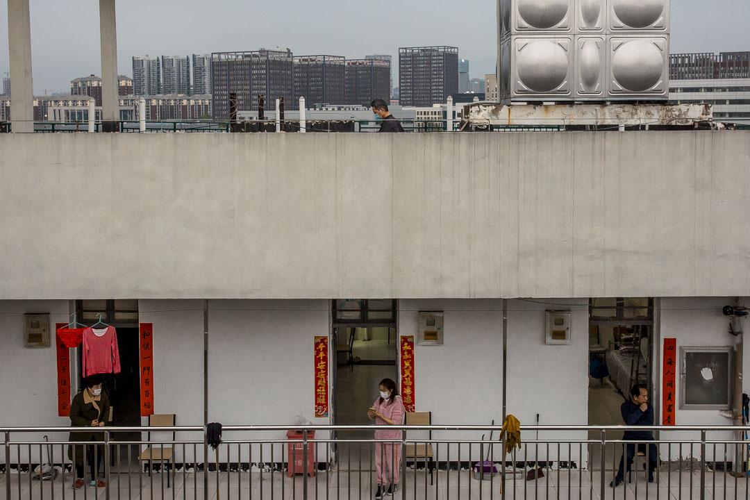 武漢軟件工程職業學院作為康復隔離點,康復病人在走廊聊天。