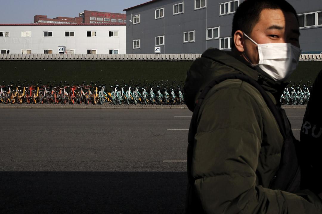 2020年2月10日,一名戴著口罩的男子站在北京地鐵站外一堆共享單車附近。