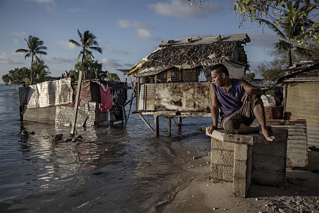 2015年9月30日,吉里巴斯村莊的居民坐在海邊,海水慢慢地淹沒他的村莊。