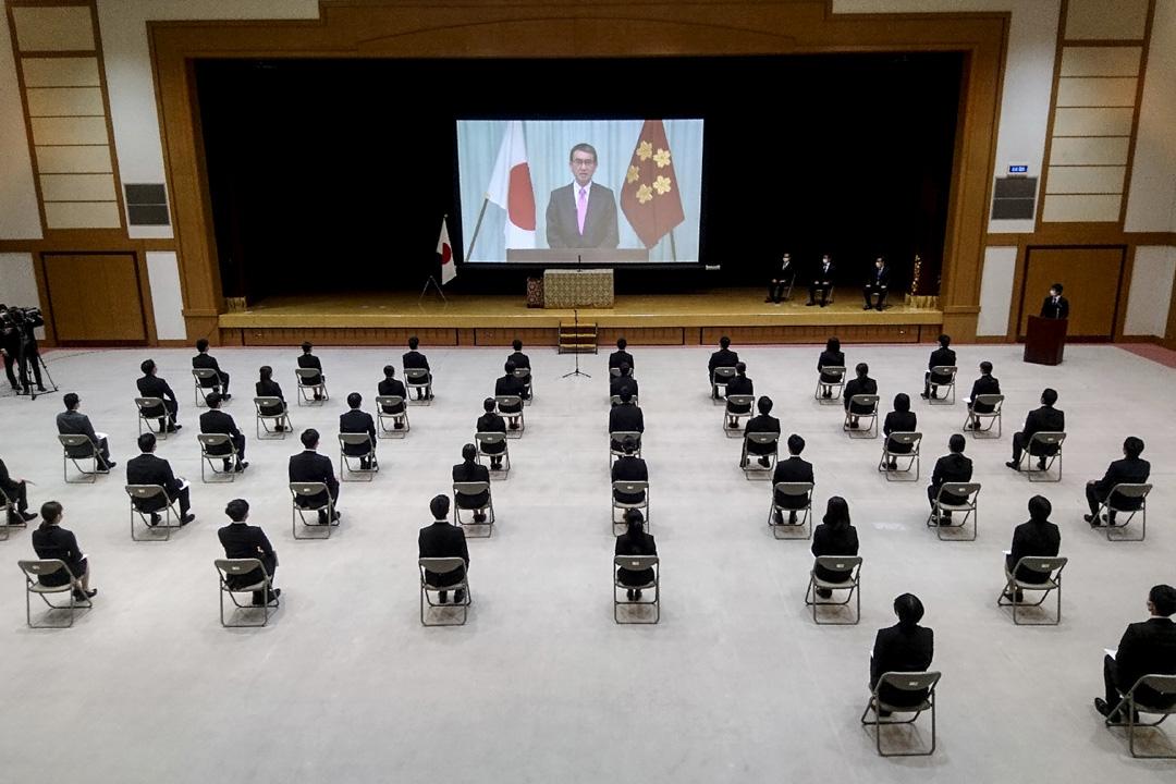 2020年4月1日,日本防衛省的新員工坐在椅上觀看國防部長河野太郎的視頻直播。