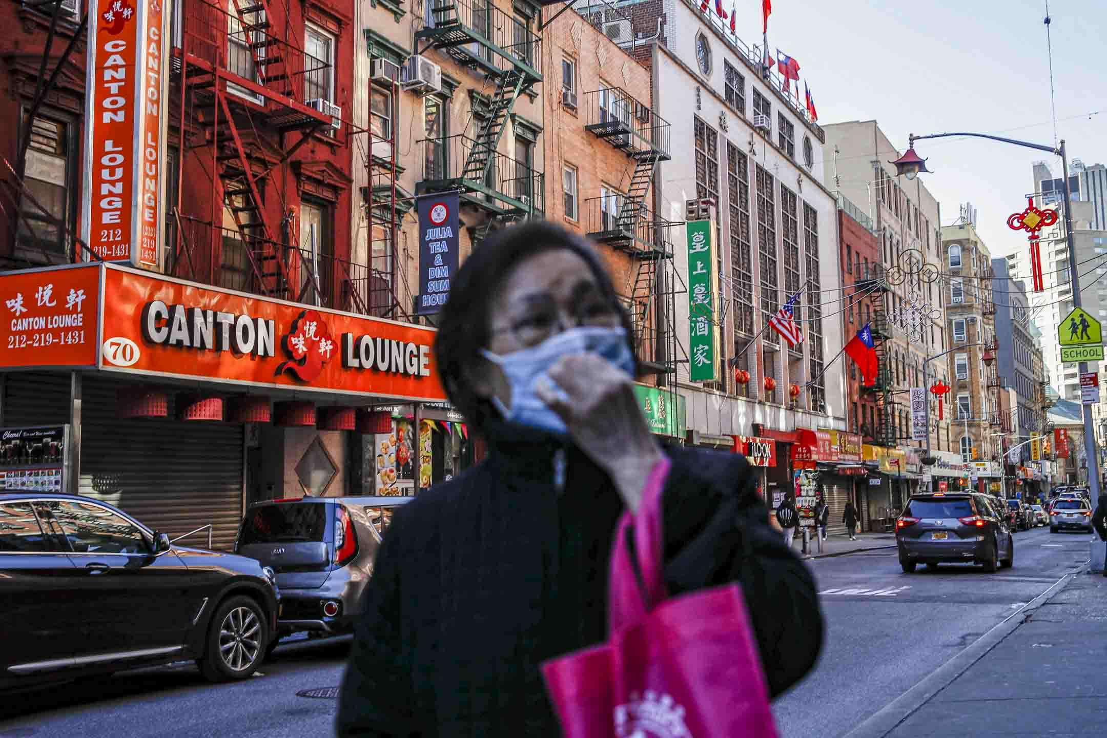 2020年3月16日,新冠疫情下的紐約唐人街,一名行人在餐館前路過。  攝:John Minchill/AP/達志影像
