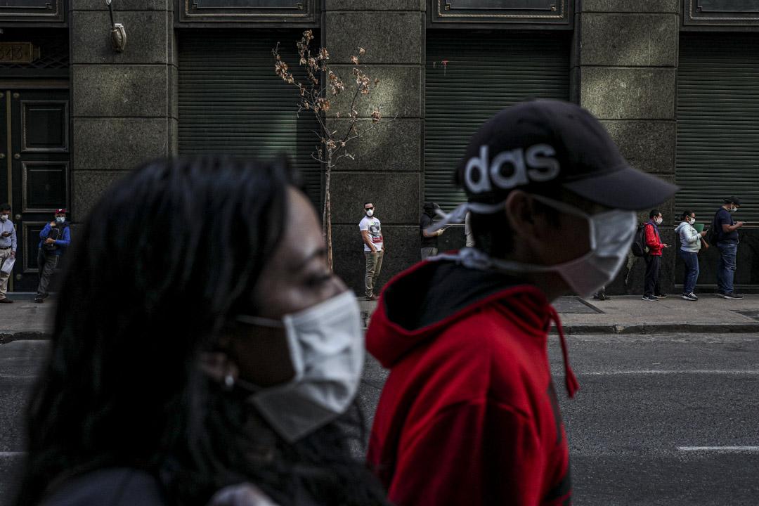 2020年4月6日智利聖地亞哥市中心,戴口罩的人排隊領取失業保險,許多人受到2019冠狀病毒引發的經濟危機影響。 攝:Esteban Felix/AP/達志影像