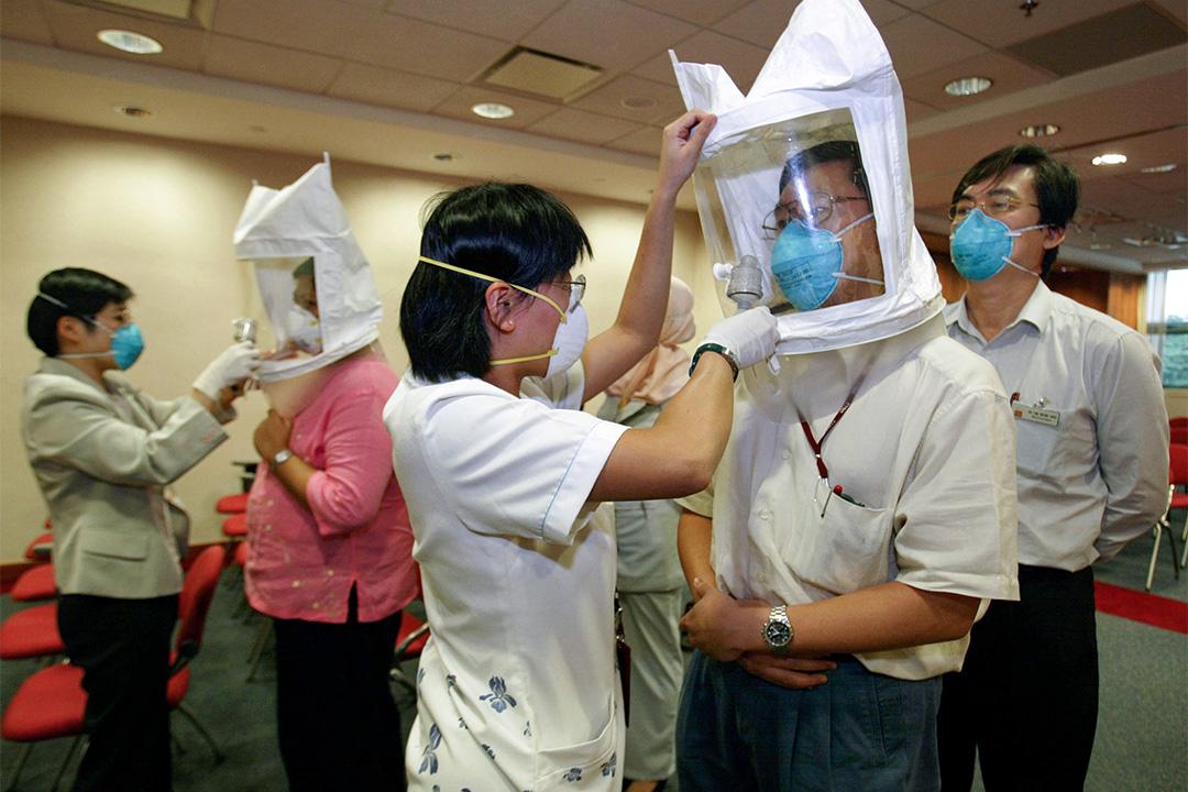 2003年4月25日新加坡,醫院的員工佩戴口罩預防嚴重急性呼吸道症候群(SARS)。