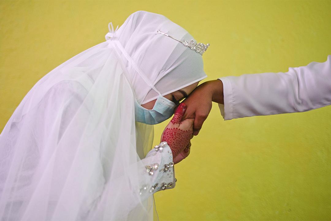 2020年3月20日馬來西亞,Nuramiraalia Noorbashah親吻新郎Mohammad Nor Azwan Ishak的手,他們戴著口罩在吉隆坡郊外蘭昌市舉行婚禮。