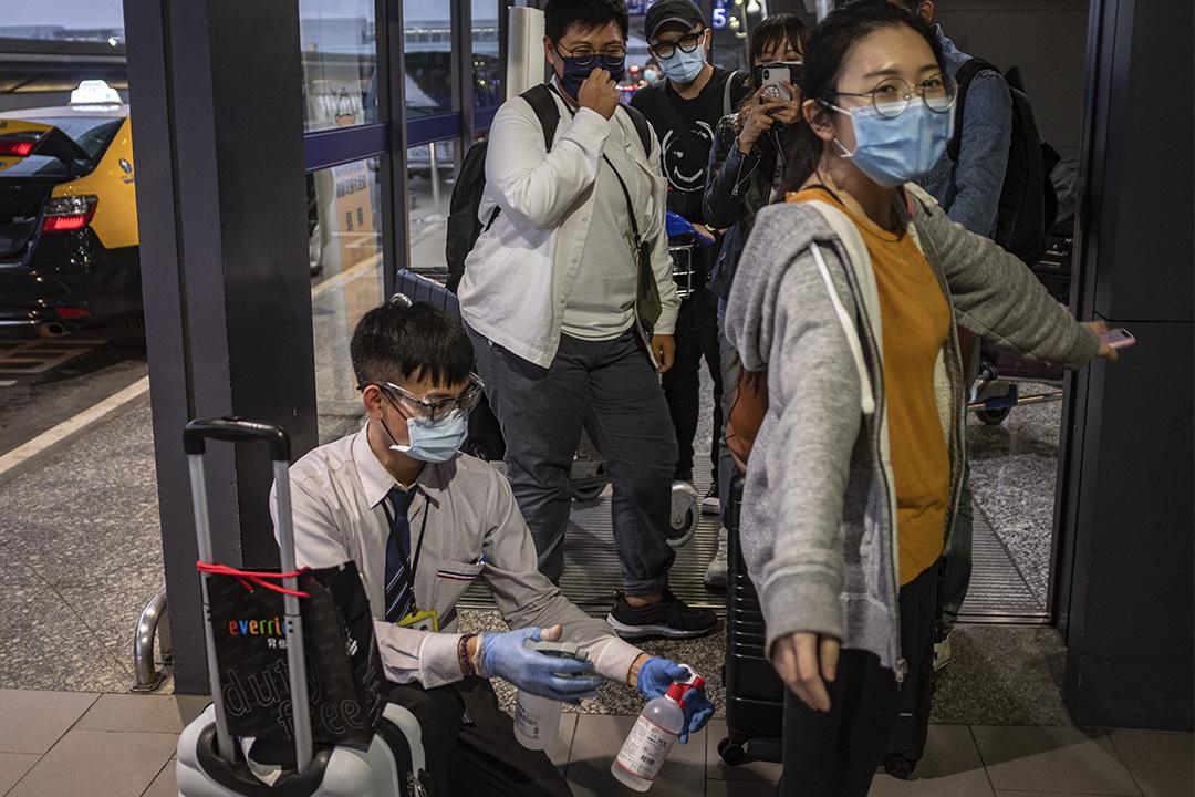 2020年3月19日,大批海外返台的民眾抵達桃園國際機場,並需消毒才可登車離開。