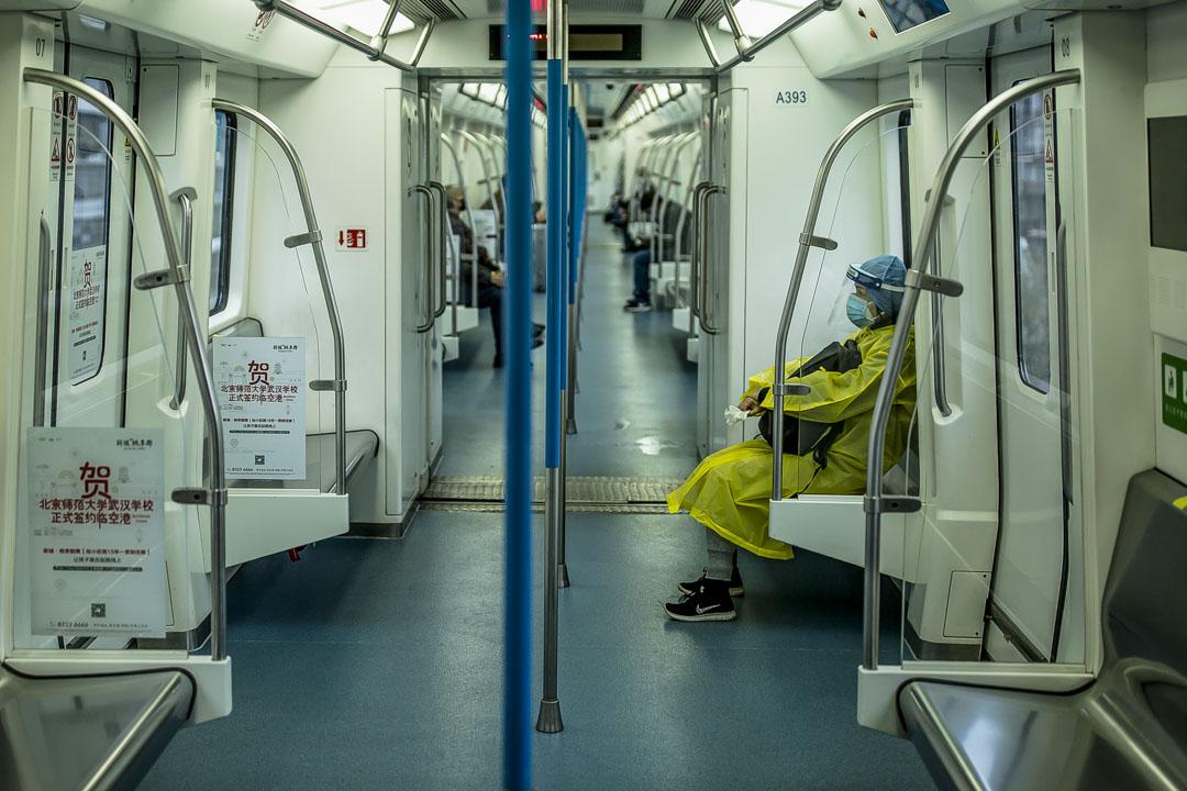武漢市地鐵恢復運營第一日,市⺠穿著防護裝備乘坐地鐵出行。