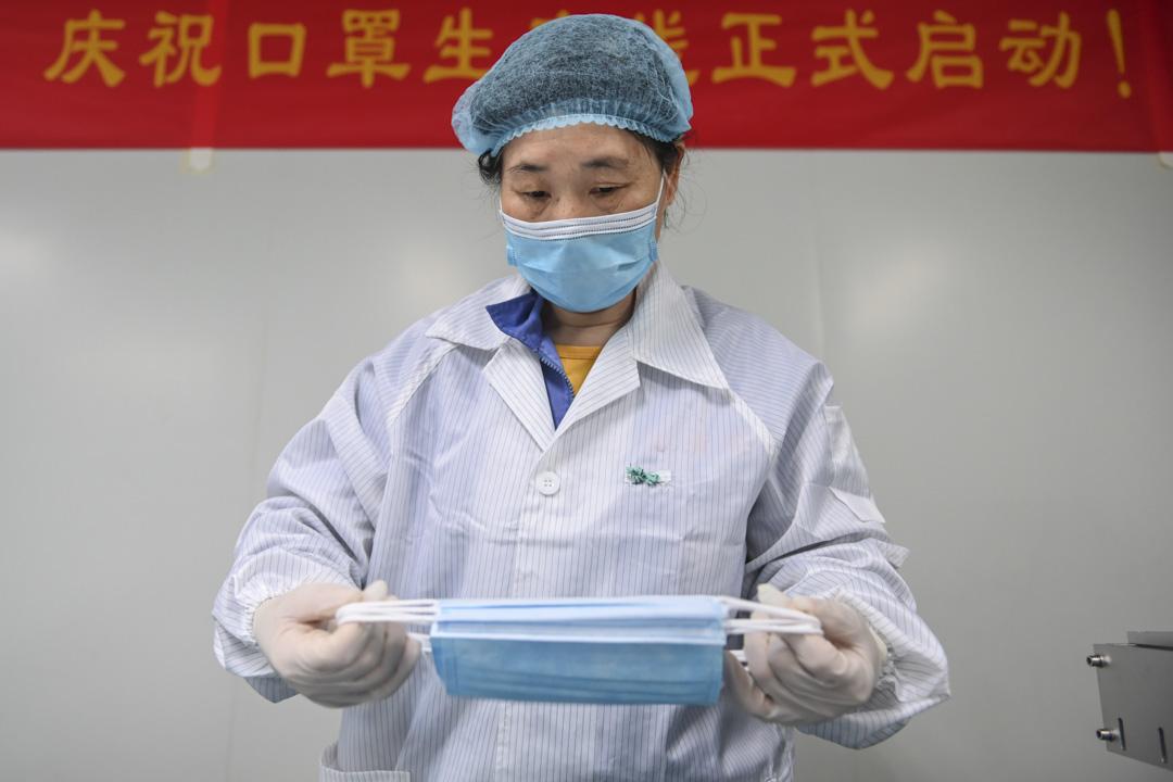 2020年4月2日,一名工人在中國廣州的一家工廠檢查在生產線上的口罩。