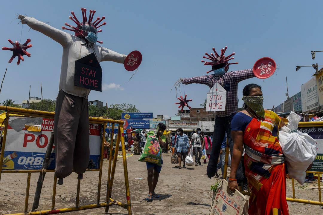 2020年4月11日,印度一名戴著口罩的婦女經過當地一個新冠病毒的模型。