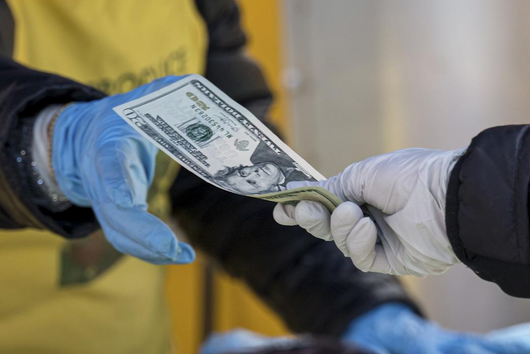 2020年3月25日,美國加州一個農貿市場上,一名戴著防護口罩和手套的商販從顧客收取美金。