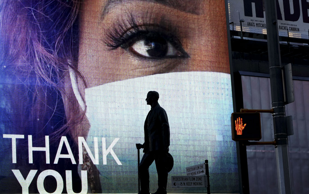 2020年4月19日,紐約時報廣場上看到作曲家喬治科漢(George M. Cohan)的雕像,屏幕顯示著對必需工作的人的感謝。