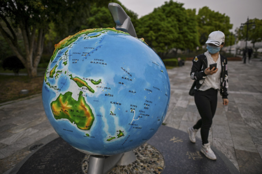 2020年4月8日,武漢市的一個公園裡,戴著口罩的女士路經一個地球儀。