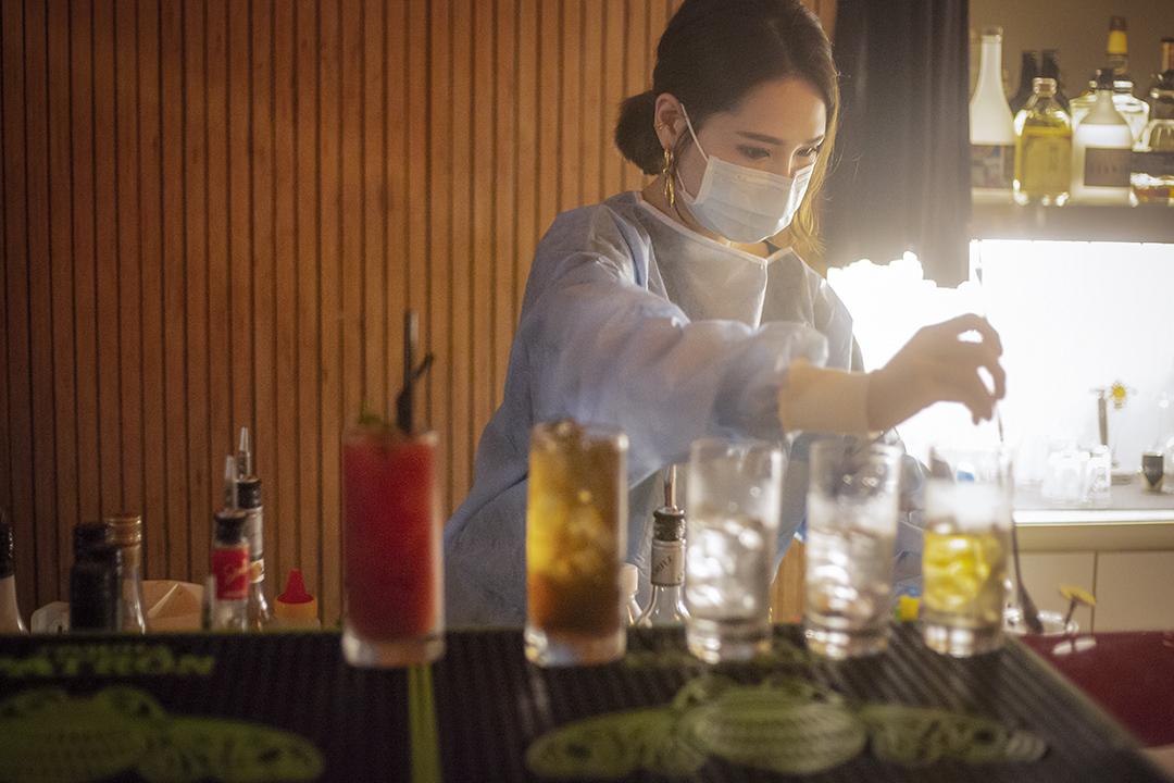 2020年4月11日,台北林森北路的一間酒吧,職員穿上防護衣調酒。